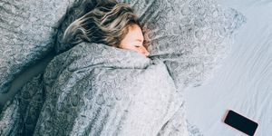 Vrouw in bed met telefoon