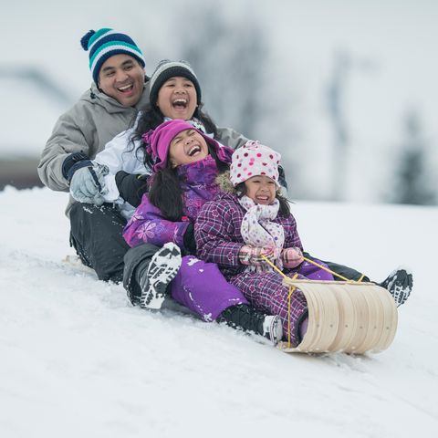 a family sledding on an old fashioned sled
