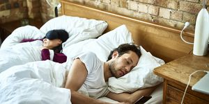 Woman fast asleep next to partner who is checking his smartphone