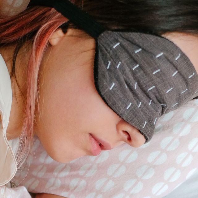 woman wearing sleep mask in bed
