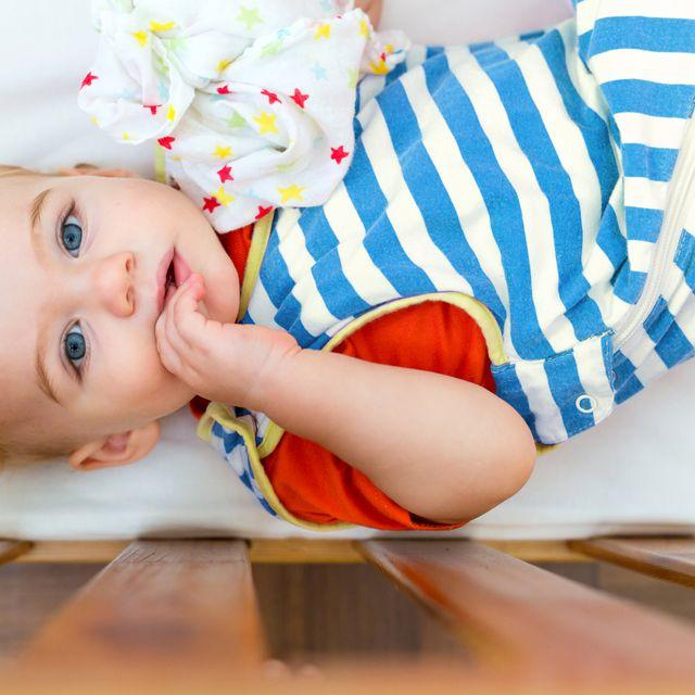 baby wearing striped sleep sack in crib