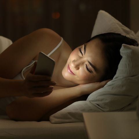 Girl using a smart phone on the bed in the night