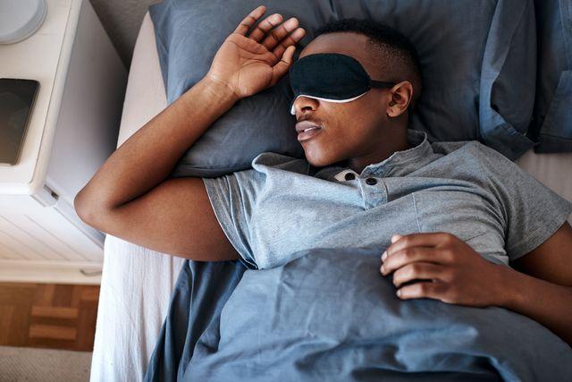 man sleeping in bed wearing eye mask