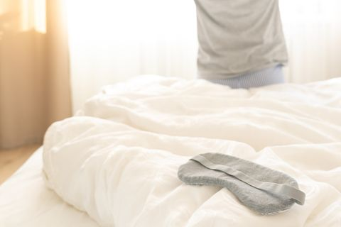 sleeping mask on a bed with stretching woman in the background