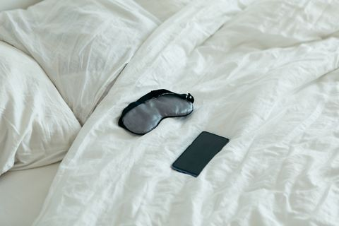 sleeping mask with phone at bed with white sheets sunny morning bedroom