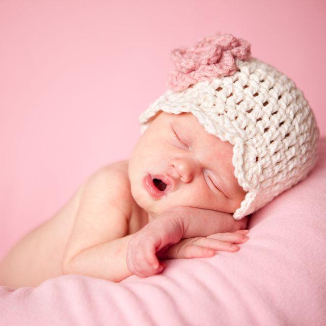 sleeping newborn baby girl wearing a crocheted hat on pink