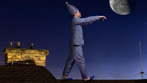 slaapwandelaar in streepjespyjama loopt op zijn dak