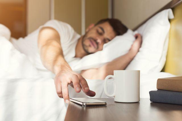 sleepy guy waking up early after alarm clock signal
