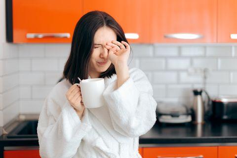 sleepy woman in bathrobe holding coffee mug