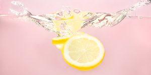 Sliced lemons splashing in water