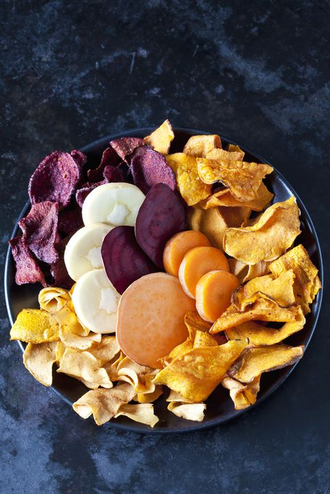 Sliced root vegetables and vegetable chips in bowl