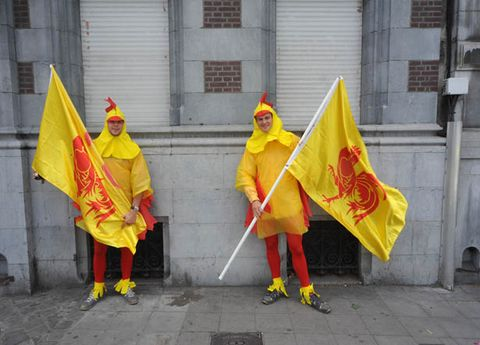 Yellow, Flag, Costume, Tradition, Costume accessory, Raincoat, Festival, Costume design, Costume hat, Cleanliness,