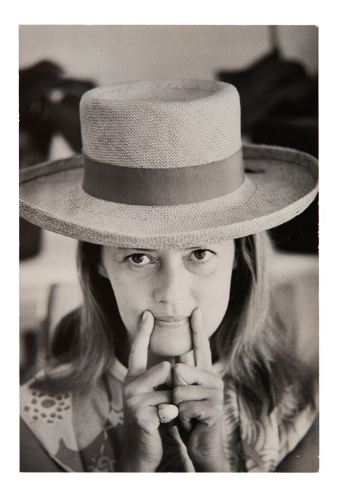 black and white photo of woman in hat, smiling