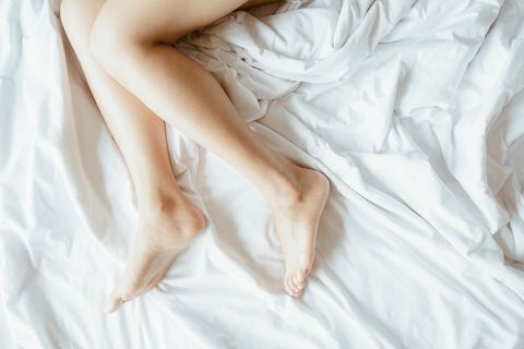slim and charming crossed woman legs on bed