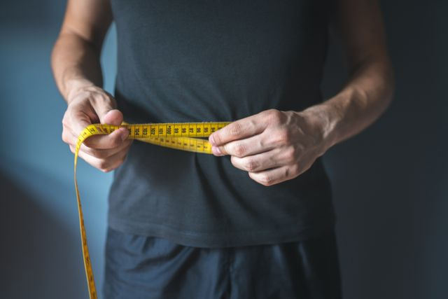 slim man measuring his waist healthy lifestyle, body slimming, weight loss concept