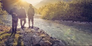 Slovenia, Bovec, three friends at Soca river at sunset