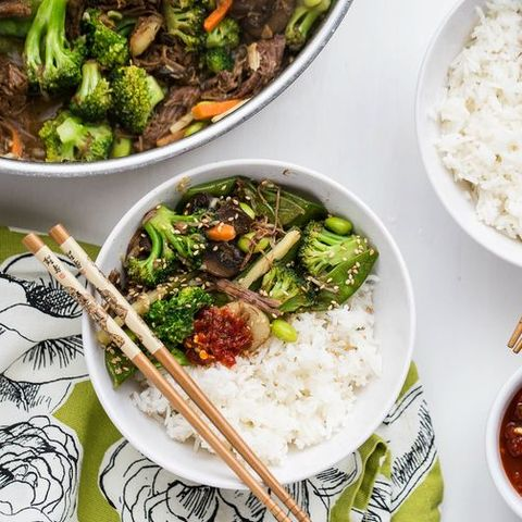 shredded beef and broccoli stir fry over rice with chopsticks