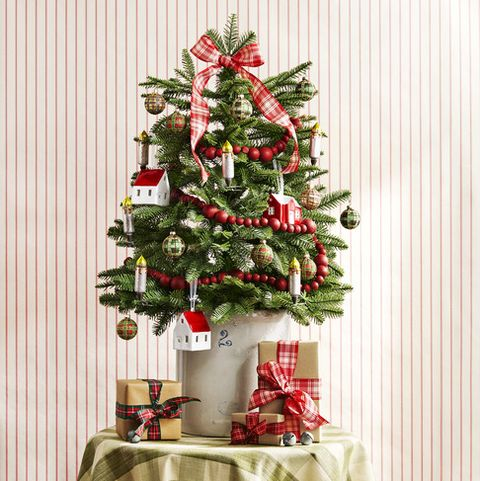 this mini balsam fir embraces traditional elements like a plaid bow and cranberry garland and tartan ornaments plus homey accents like clip on candlesticks and a stoneware crock serves as a classic base