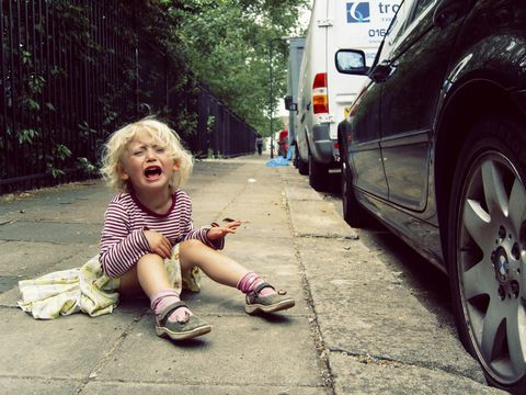 small girl having a tantrum on the pavement