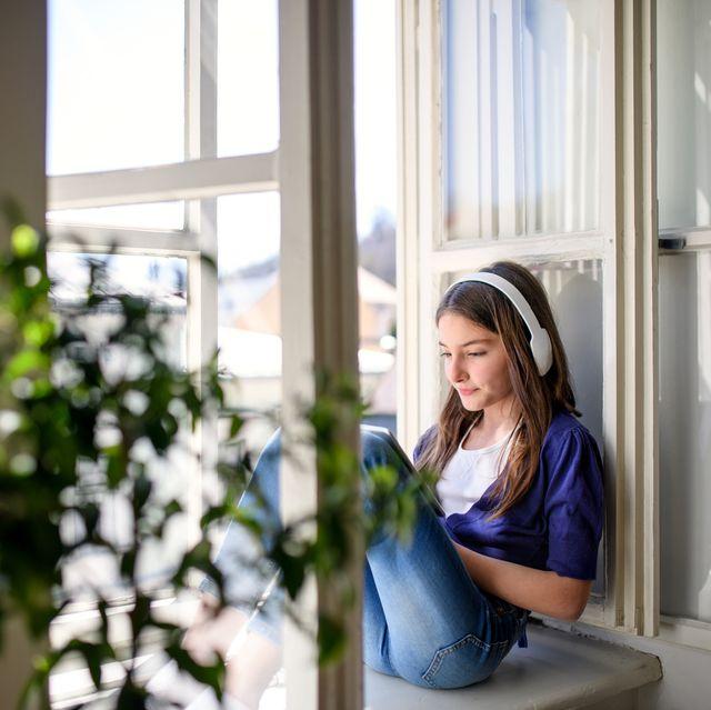 small schoolgirl sitting on window sill