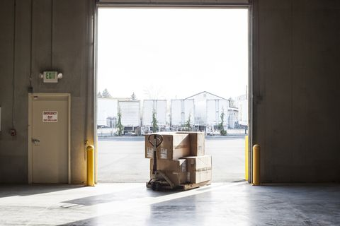 A small stack of products in boxes sitting on a manual pallet jack in a loading dock door at a distribution warehouse.