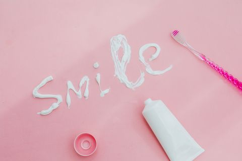 smile message with toothpaste , toothbrush in pink