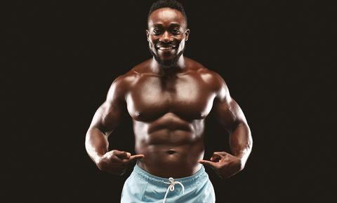 Smiling african fitness model pointing at his six packs
