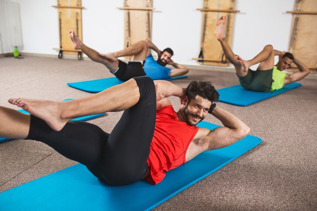 smiling athletic man doing sit ups in health club