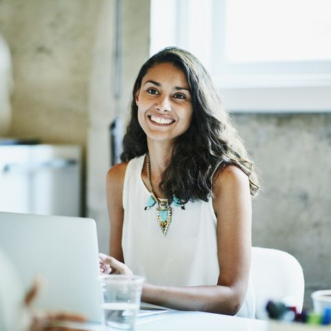 Smiling businesswoman in discussion with colleagues during meeting in office conference room