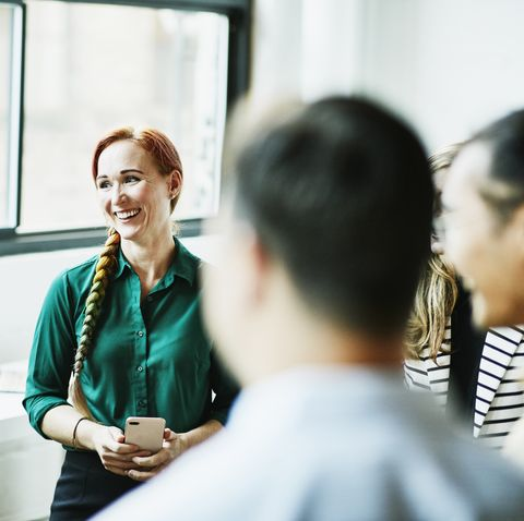 smiling businesswoman listening during team meeting in office