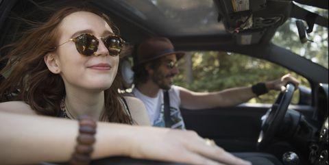 Smiling, carefree woman enjoying breeze, riding in car on road trip