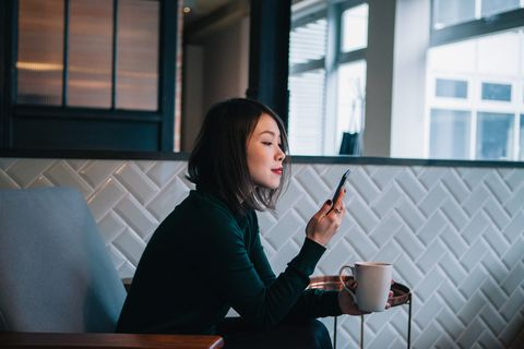 smiling, confident, modern businesswoman taking coffee break and checking social media at mobile phone in office