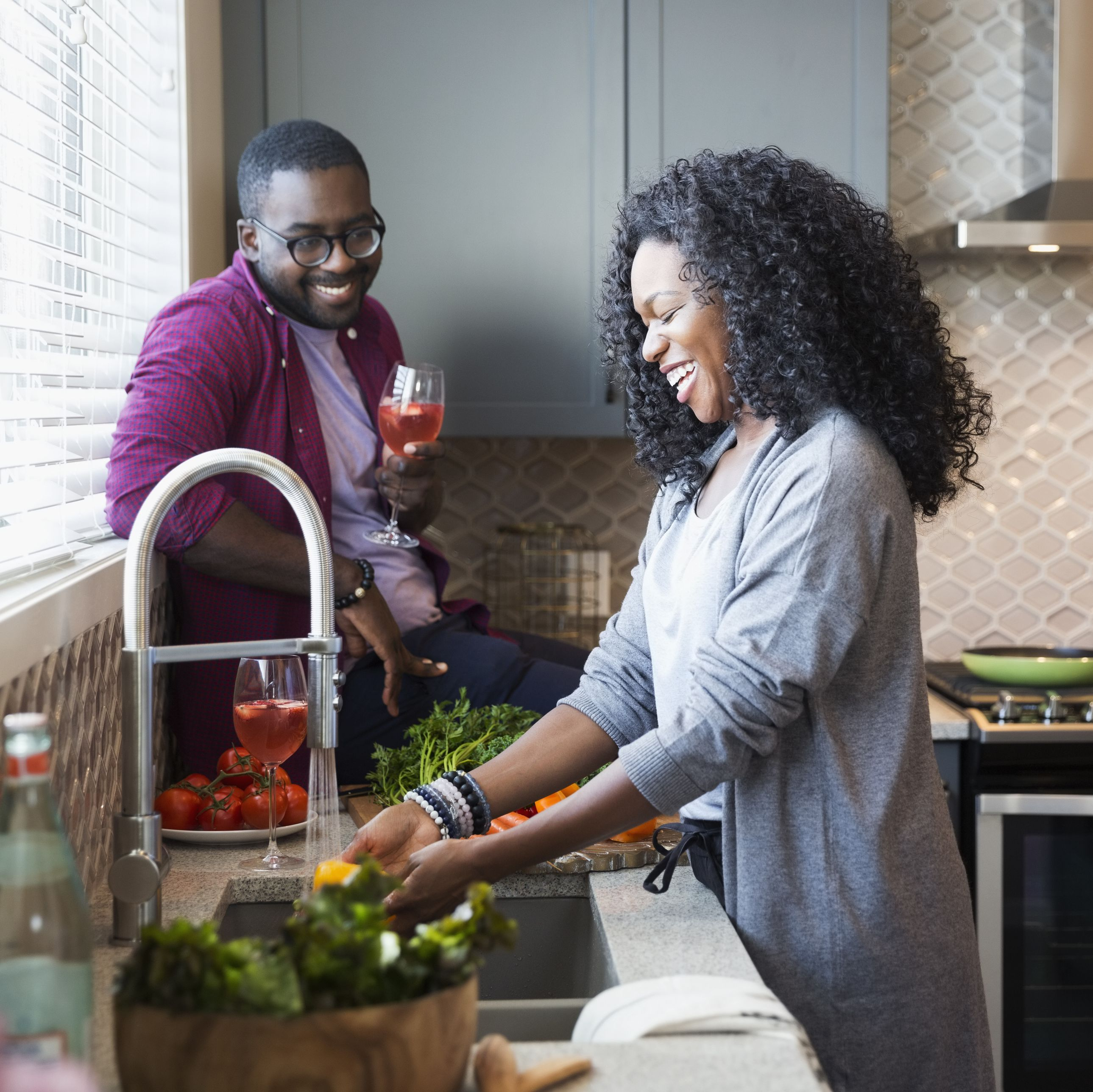 Smiling couple drinking sangria and washing vegetables at sink in kitchen