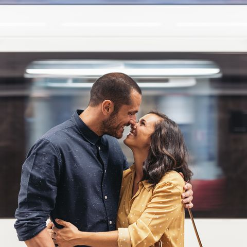 smiling couple kissing while standing at railroad station platform