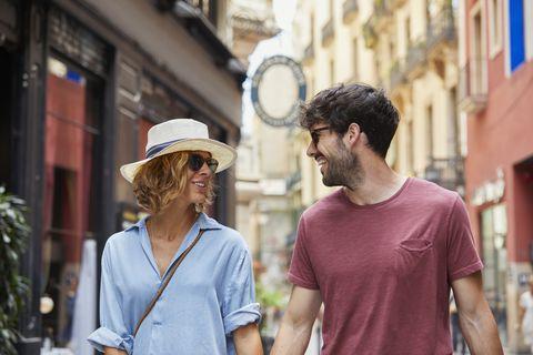 Smiling couple walking on street in Barcelona