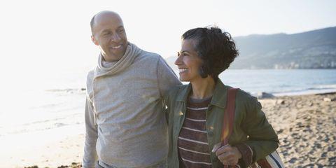 Smiling couple walking on sunny beach