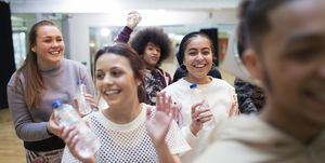 Smiling, enthusiastic teenage girls drinking water and cheering in dance class in studio