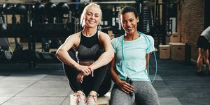 Smiling female friends sittting at the gym after working out
