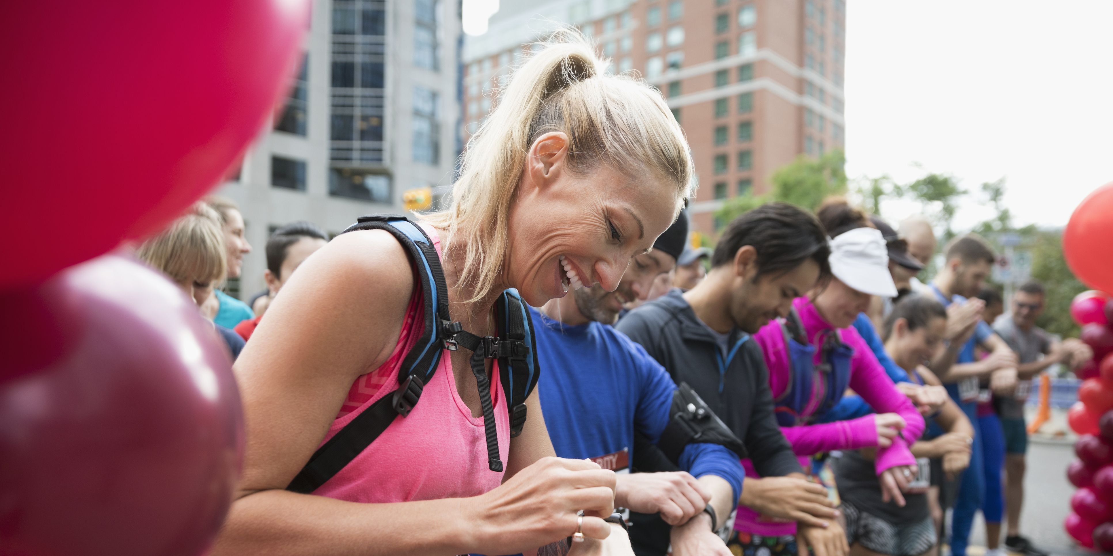 Smiling female marathon runner ready, preparing smart watch at starting line on urban street