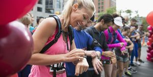Smiling female marathon runner ready, preparing smart watch at starting line on urban street