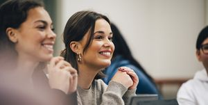 Smiling female students looking away while sitting in classroom
