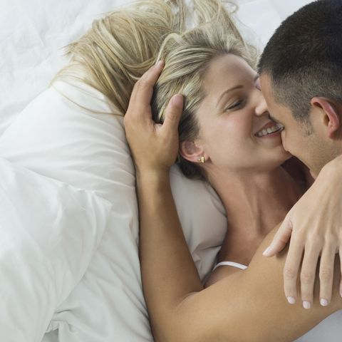 smiling hispanic couple laying in bed