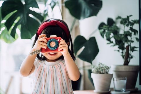 smiling little asian girl with red headband acting like a professional photographer having fun while taking photos with wooden toy camera in front of potted plants at home