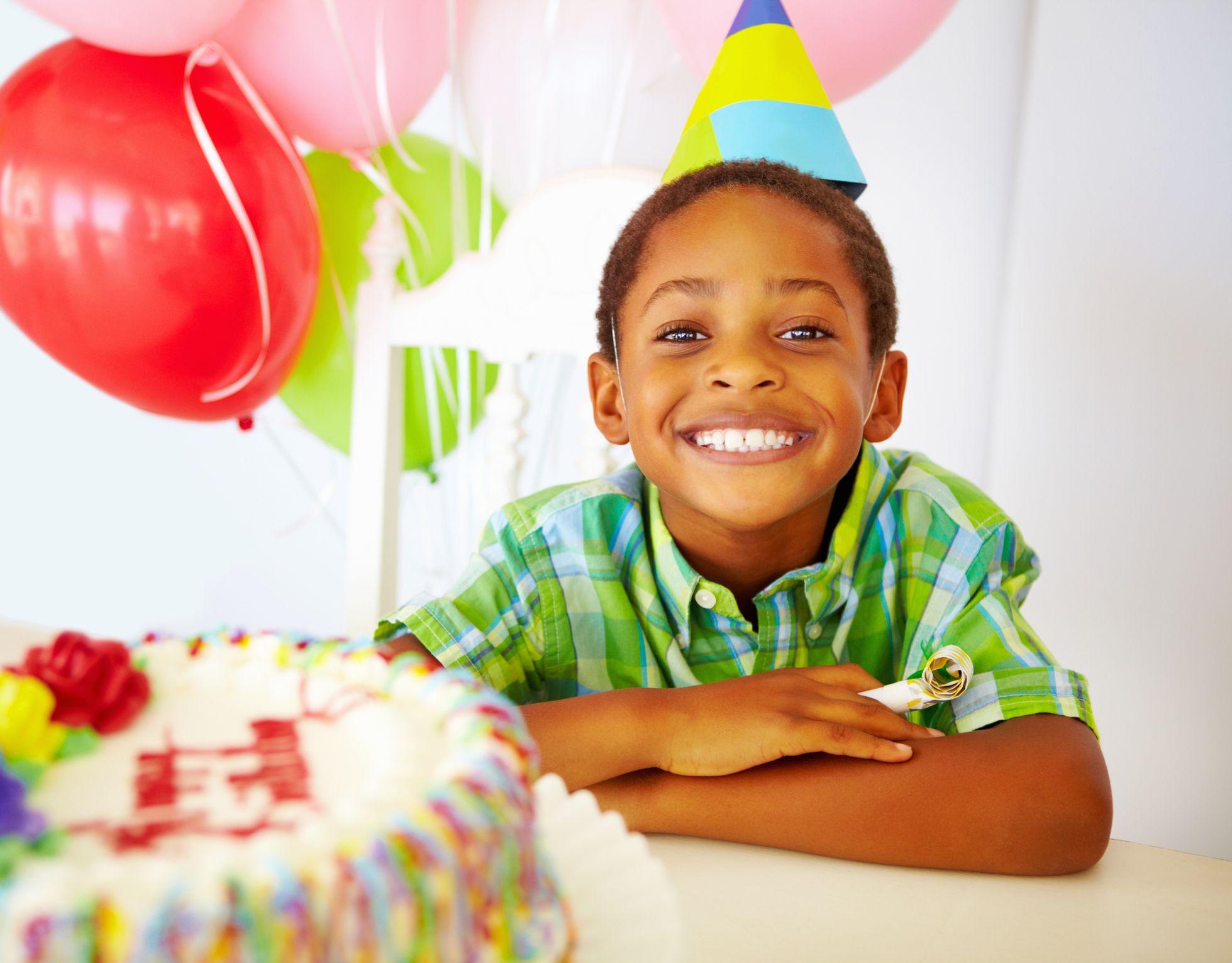 naeratav väike poiss sünnipäevapeol koogi ees