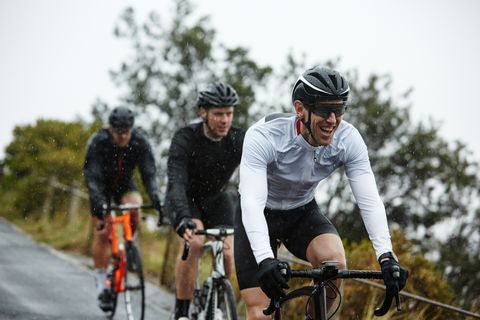 Smiling male cyclist cycling with friends
