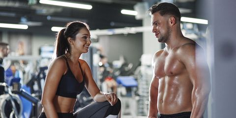 Smiling man and woman talking at the gym
