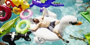 Smiling man relaxing on inflatable swan in pool