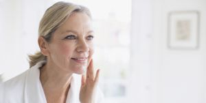 Smiling mature woman applying moisturizer to face at bathroom mirror