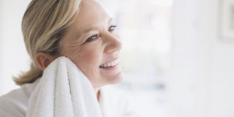Smiling mature woman drying face with towel
