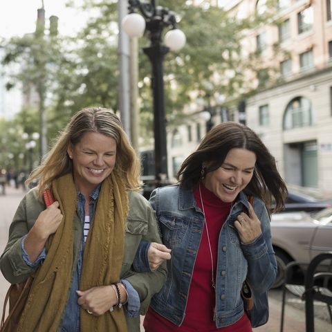 Smiling mature women friends walking arm in arm on urban sidewalk